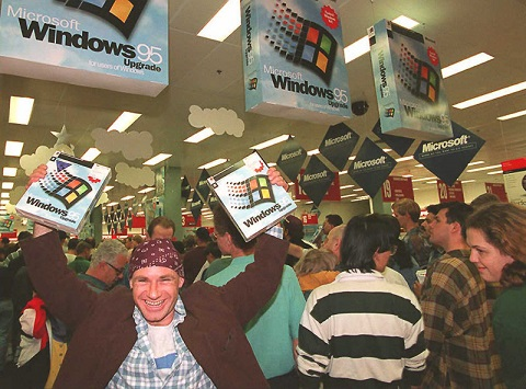 SYDNEY, AUSTRALIA - AUGUST 24:  Mikol Furneaux(L) waves two packages of Windows 95 software in the first store in Australia to sell the product at midnight 24 August.   Microsoft hopes to sell between 20 and 30 million copies of the software world wide by the end of 1995. AFP PHOTO  (Photo credit should read TORSTEN BLACKWOOD/AFP/Getty Images)